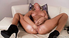 Blonde in high heels gives her cunt a stuffing with her fist
