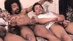 Three black studs lie side by side on the bed stroking their big cocks