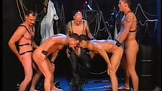 Handsome boy toy in leather straps gets spit roasted in a kinky gay orgy