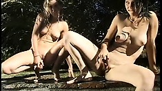 In the outdoors, two wild lesbian babes with perfect bodies have fun with dildos